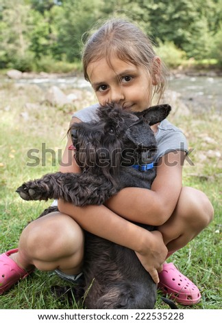 Smiling little girl hugging her lovely dog, resting together outdoors - stock photo