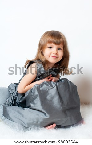 Smiling little girl in a beautiful dress sitting in the studio