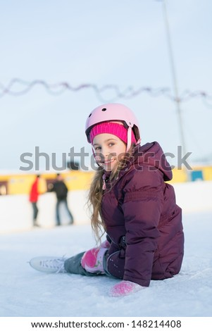 Smiling little girl in a helmet and knee pads sitting at the rink in winter
