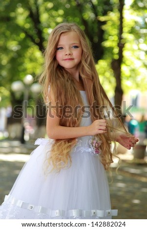 smiling little girl in a white ball gown in the summer park outdoors - stock photo