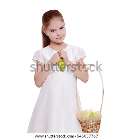 Smiling little girl in a white dress holding colored easter egg on Holiday