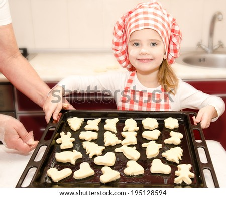 Smiling little girl in chef hat with baking sheet of cookies in the kitchen - stock photo