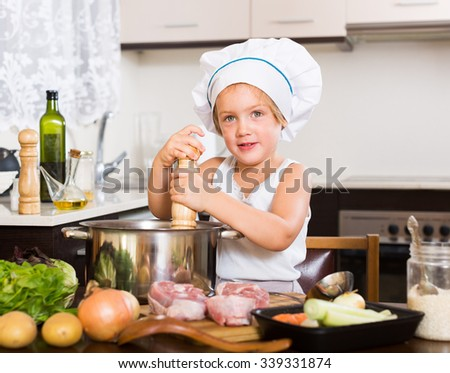 Smiling little girl in chefâ??s hat cooking food at home kitchen