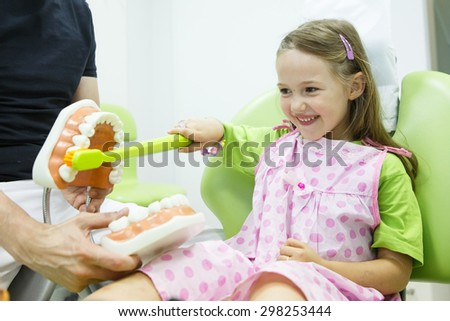 Smiling little girl in dentists chair, being educated about proper tooth-brushing by her paediatric dentist. Early prevention, raising awareness, oral hygiene demonstration concept.  - stock photo