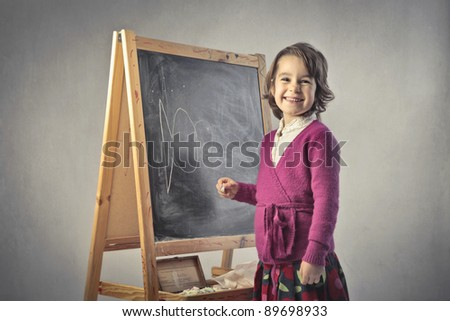 Smiling little girl in front of a blackboard - stock photo