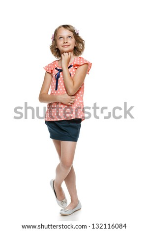 Smiling little girl in full length standing over white background and looking up - stock photo