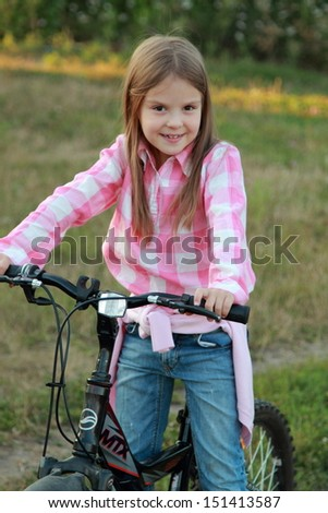 Smiling little girl in jeans sitting on the bike
