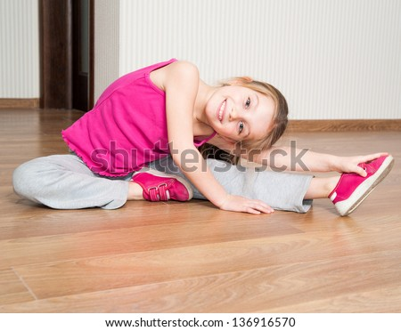 smiling little girl in pink engaged in fitness at home - stock photo