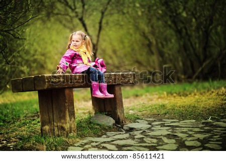 smiling little girl in raincoat and boots outdoor - stock photo