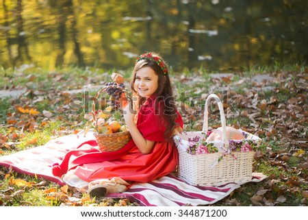 Smiling little girl in red clothes and flower wreath on frizzy dark hair holding blue bunch of grapes on plaid with picnic baskets on lawn near lake in autumn park, horizontal photo - stock photo