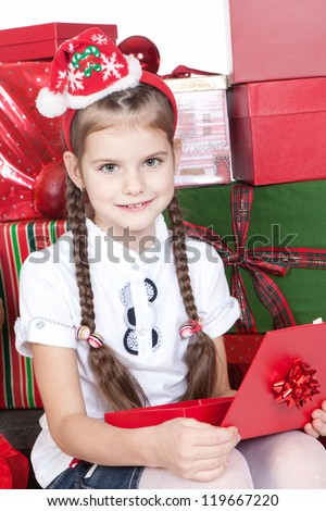 Smiling little girl in Santa's Helper hat holding red gift