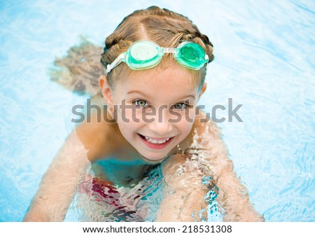 smiling little girl in swimming pool - stock photo