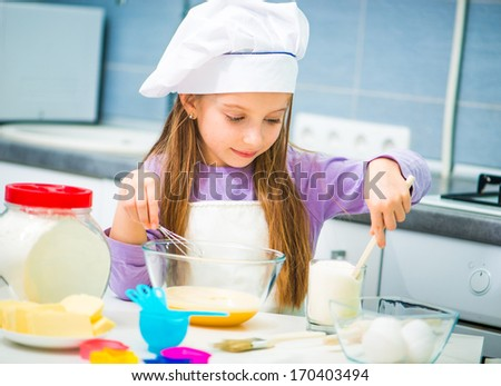 Smiling little girl in the kitchen preparing cookies - stock photo