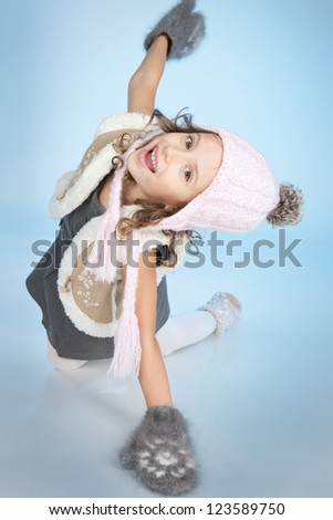 Smiling little girl in winter clothing at winter time over blue