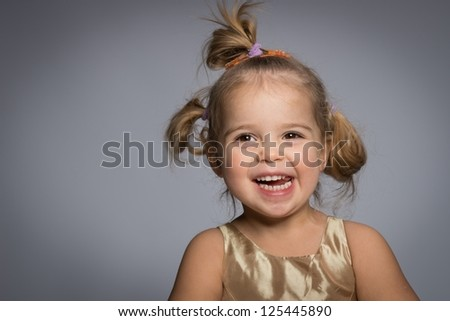 Smiling little girl isolated on grey