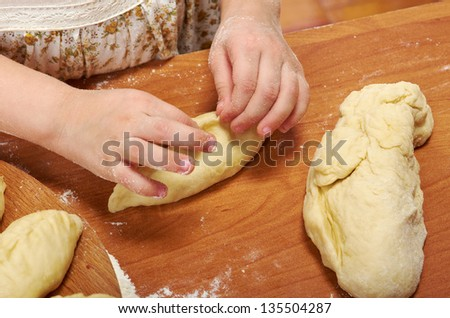 Smiling little girl kneading dough at kitchen .Detail of hands kneading dough