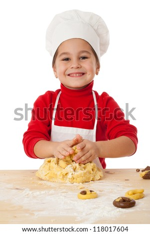 Smiling little girl kneading the dough for cookies, isolated on white - stock photo