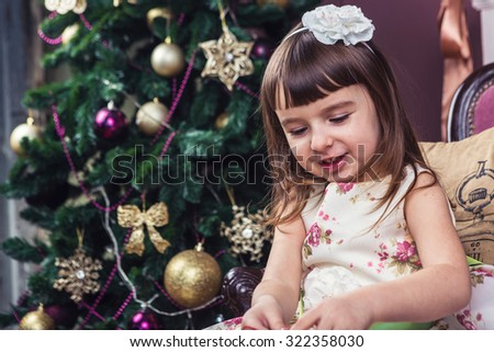 Smiling little girl looking down. The family atmosphere of the winter holidays. Cozy and warm house mood.  Merry Christmas and happy New Year! A series of photos - stock photo