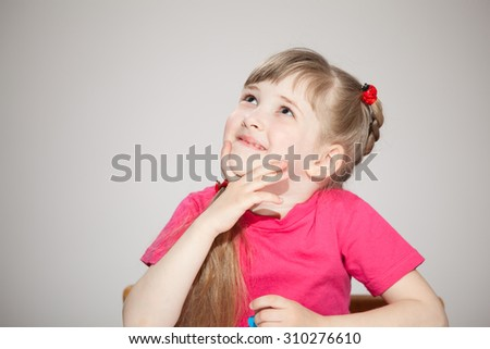 Smiling little girl  looking up, gray background - stock photo