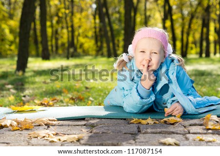 Smiling little girl lying on a mat in the park making shushing gesture raising her finger to her lips as a sign of silence or secrecy - stock photo