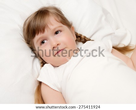 Smiling little girl on a bed - stock photo