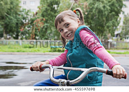 Smiling little girl on a bicycle. - stock photo