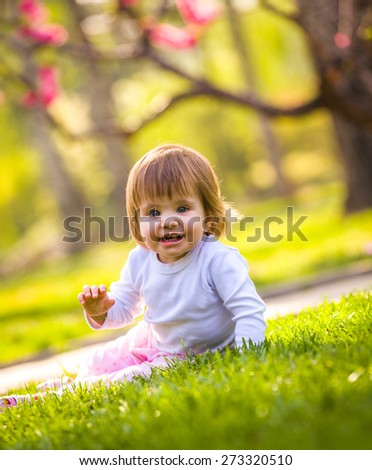 Smiling little girl on a meadow - stock photo
