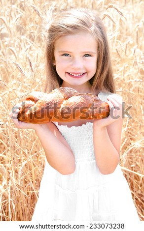 Smiling little girl on field of wheat with bread  - stock photo