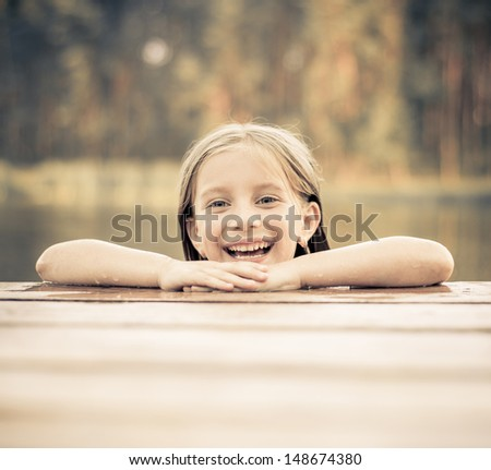 smiling little girl on the bridge in the river - stock photo