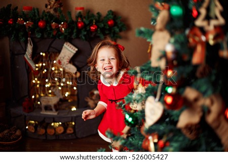 Smiling little girl peeping from behind Christmas tree in living room. Horizontal indoors shot