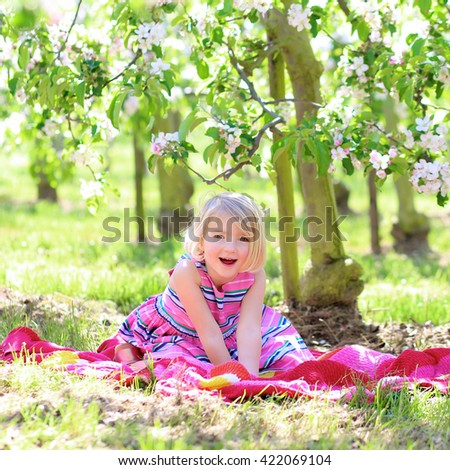 Smiling little girl playing in blooming fruit garden. Kid enjoying happy childhood. Family, love, peace and happiness concept. - stock photo