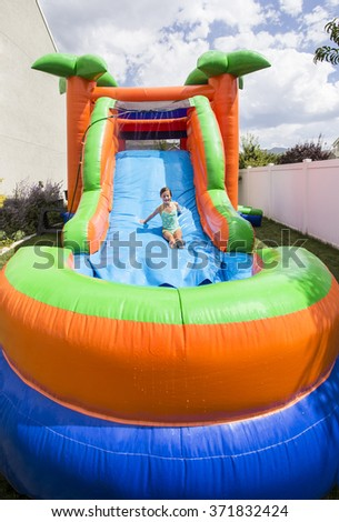 Smiling little girl playing on an inflatable slide bounce house outdoors - stock photo