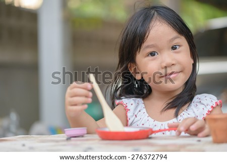 Smiling little girl plays cook on the table - stock photo