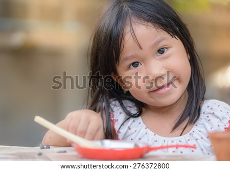 Smiling little girl plays cook on the tables