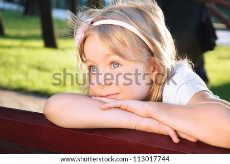 smiling little girl portrait at a park on summer sunny day - stock photo