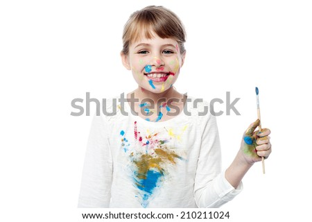 Smiling little girl posing with paint brush - stock photo
