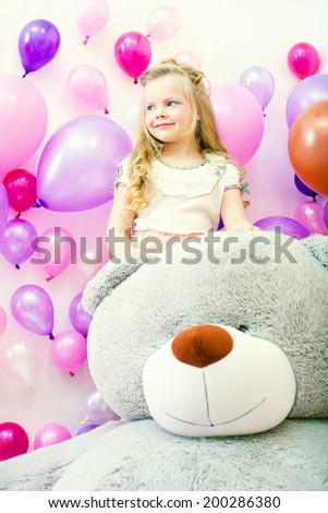Smiling little girl posing with plush bear - stock photo