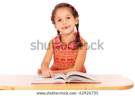 Smiling little girl reading book on the desk, isolated on white