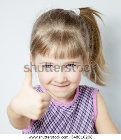 Smiling little girl showing thumb up - closeup portrait - stock photo