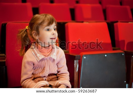 Smiling little girl sitting on armchairs at cinema - stock photo