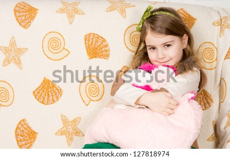 Smiling little girl sitting on her bed hugging her favourite soft plush toy tightly to her chest against seashell patterned linen with copyspace - stock photo