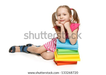 Smiling little girl sitting on the floor leaning on the stack of books, over white background - stock photo