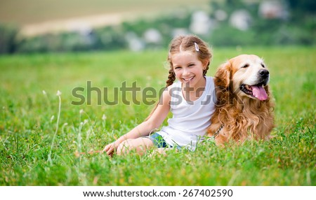 Smiling Little girl sitting on the grass with golden labrador - stock photo