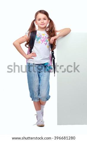Smiling little girl standing near empty white board - stock photo
