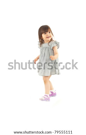Smiling little girl walking and looking away isolated on white background