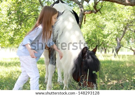 smiling little girl walking with a charming pony in the apple garden/Pony in the meadow eating green grass - stock photo