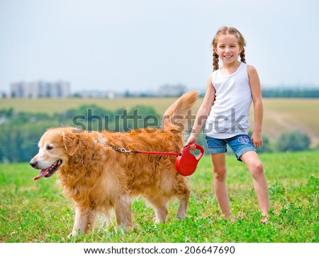 Smiling little girl walks on the leash with a golden retriever