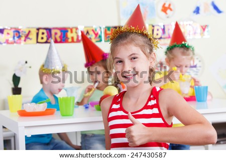 Smiling little girl wearing party hat is looking at the camera. Other children are in the background.