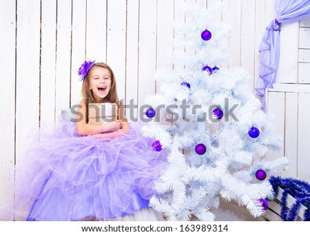 smiling little girl with a gift in hands near Christmas tree - stock photo