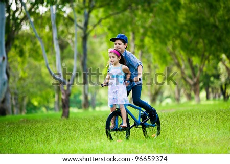 Smiling little girl with a heart in the park - stock photo